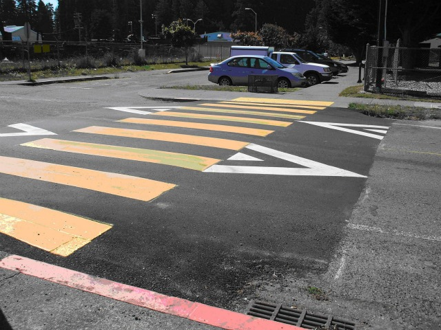 Raised crosswalks are flat-topped road bumps built as a pedestrian crosswalk with vehicle ramps on the approaches. They are vertical deflections installed across a roadway to reduce speed and create a safer crossing environment for pedestrians by making them more visible to approaching drivers.